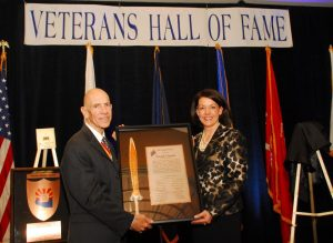 The 2014 recipient of the Copper Sword Award at the Patriotic Gala of the Veterans Hall of Fame holding the frame of the award with the announcer.