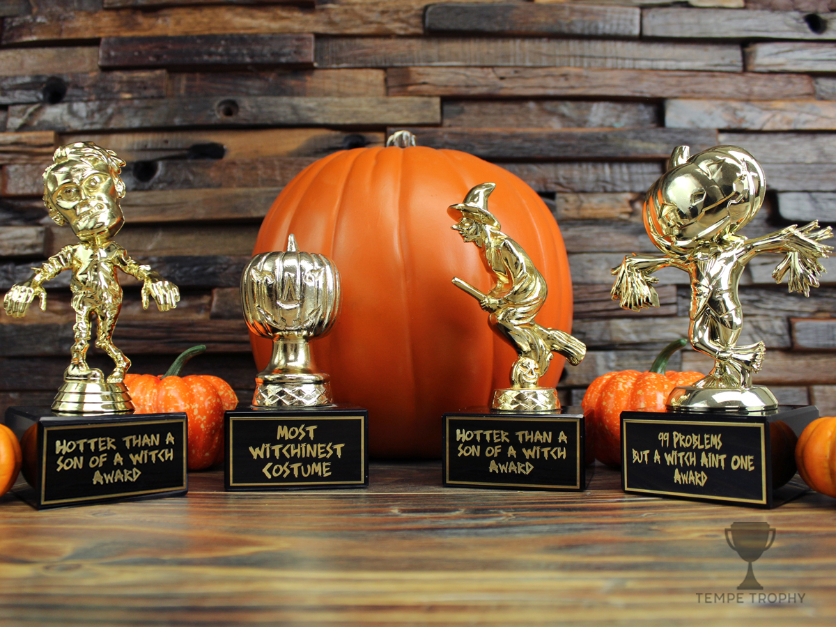 A Zombie, Jack-o-Lantern, Witch, and Scarecrow trophy in front of pumpkins.