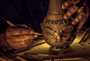 Odd Rodney's hand shot sculpting the Deadhead Rum shrunken head bottle.