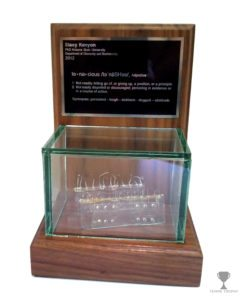 Display case holding a prototype with a plaque engraved by Tempe Trophy.