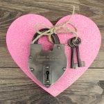 Engraved silver hand-forged love lock on top of a pink heart