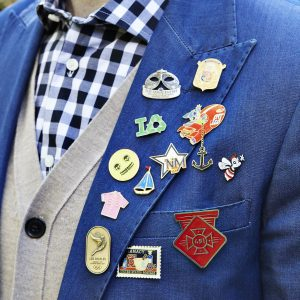 Custom made lapel pins arrayed on the lapel of a blue mens jacket